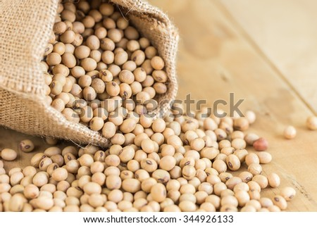 Close up soy beans in sack on wooden desk