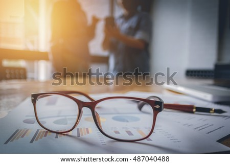 close up spectacles with ofountain pen over turnover graph paper it on wood desk in office.