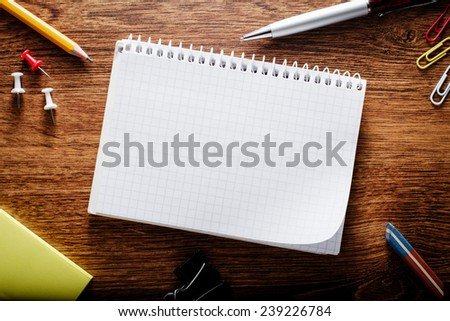 Close up Spiral Blank Graphing Notebook with Other School Supplies on Brown Wooden Table with Copy Space for Texts - stock photo
