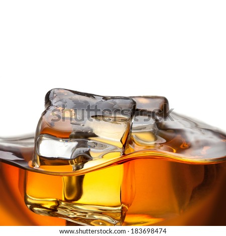 Close up splash of whiskey with ice isolated on white - stock photo
