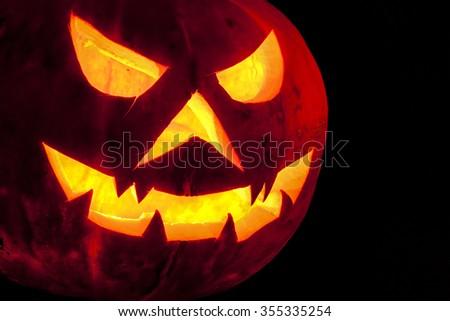 Close up spooky halloween pumpkin Jack O Lantern shiny inside on black - stock photo