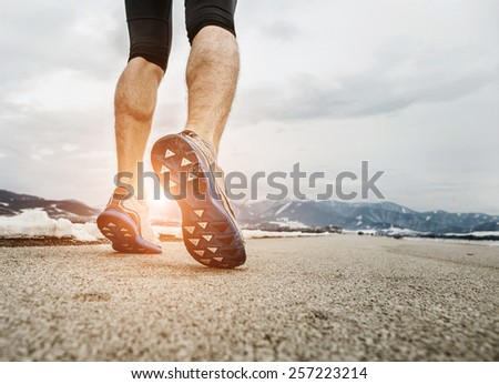 Close up sprinter legs on asphalt - stock photo