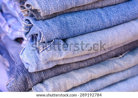 Close up stack of blue jeans background. - stock photo