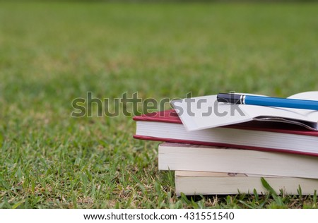 Close up stack of books putting on grasses in the garden. Background concept.