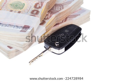 Close up stacks of banknotes with car key (shallow DOF picture) ,Isolated on white background  - stock photo