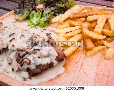 Close up steak pork with mushroom sauce, french fries and salad on wood plate.