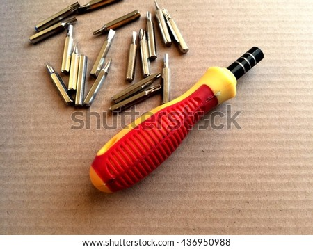 Close up steel nuts with screwdriver on cardboard background. - stock photo