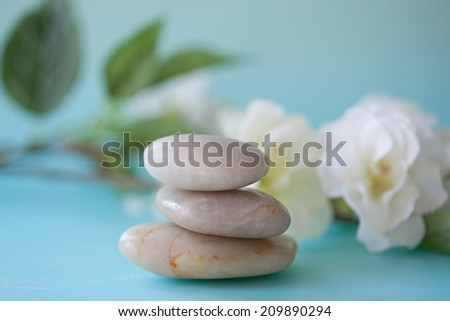 Close up still life detail view of a pile of natural smooth white stones balancing in a stack against white blossom flowers in a blue health spa background. Nature objects and zen energy. - stock photo
