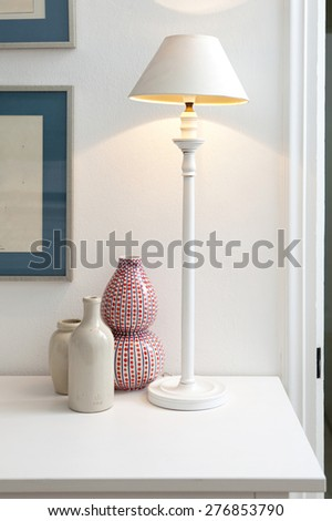 Close up still life detail view of two decorative porcelain pieces sitting together on a fireplace mantelpiece next to a lit lamp, house interior design. Aspirational lifestyle, indoors.