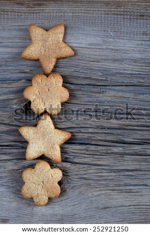 close-up still-life of Cookies in the shape of snowflakes, hearts and stars on magic Christmas holiday on background wooden boards studio