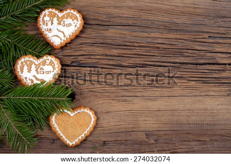 close-up still-life of fir branches and the gingerbread with pattern on magic Christmas holiday on background a wooden boards studio - stock photo