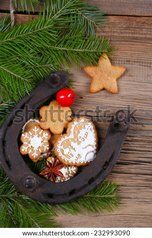 close-up still-life of fir branches, the horseshoes and gingerbread with pattern on magic Christmas holiday on background a wooden boards studio