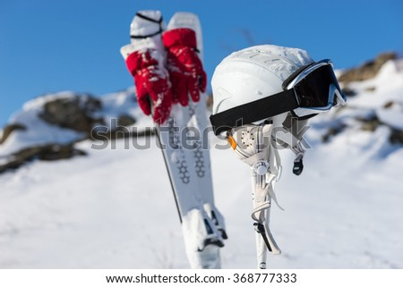 Close Up Still Life of Helmet, Goggles and Red Gloves Hanging from Skis and Poles on Snowy Hillside on Sunny Day with Bright Sunshine and Blue Sky