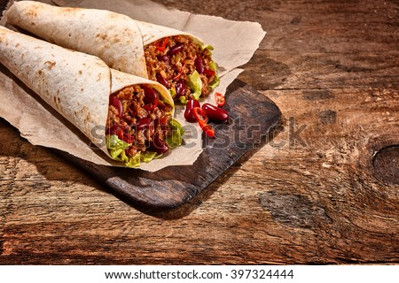 Close Up Still Life of Pair of Chili Stuffed Tex Mex Fajita Wraps Wrapped in Grilled Flour Tortillas and Resting on Rustic Cutting Board on Wooden Table with Copy Space - stock photo