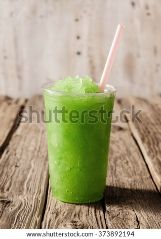 Close Up Still Life of Plastic Cup Filled with Refreshing Frozen Green Slush Drink and Served on Rustic Wooden Table with Drinking Straw - stock photo