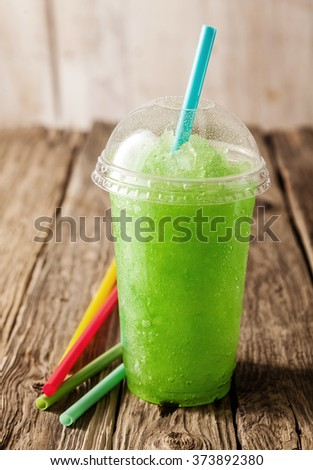 Close Up Still Life of Plastic Cup Filled with Refreshing Frozen Green Slush Drink and Served on Rustic Wooden Table with Colorful Drinking Straws - stock photo
