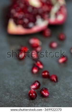 Close Up Still Life of Ripe Pomegranate on Gray Surface - Juicy Seeds of Pomegranate with Split Fruit in Background - stock photo