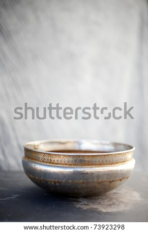 Close-up  still life photograph of a weathered metal bowl from India.