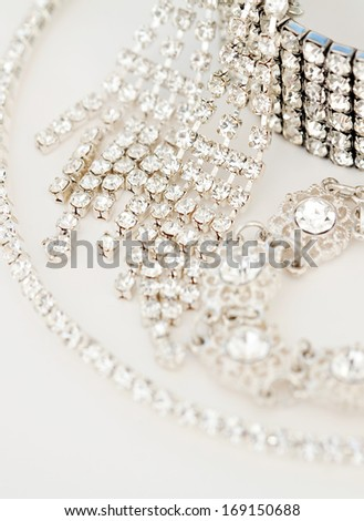 Close up still life view of exclusive and luxurious diamond bracelets, engagement rings, necklaces and earrings. A multiple quality diamond detail jewelry shining and sparkling with light, interior. - stock photo