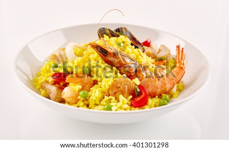 Close Up Still Life View of Traditional Spanish Paella Dish Made with Yellow Saffron Rice and Fresh Seafood and Shellfish Served in Modern White Bowl on White Background - stock photo