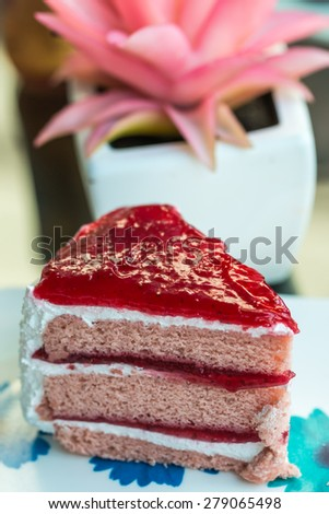 close up strawberry layer cake on white dish