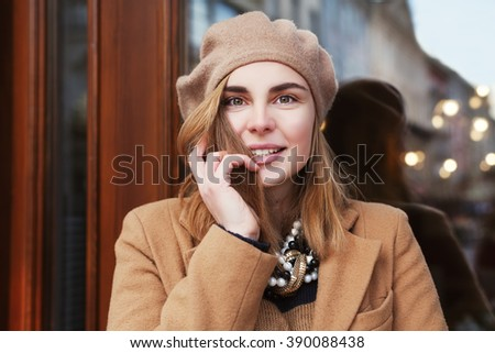 Close up street portrait of young beautiful happy smiling woman. Lady looking at camera. Model posing near the door with reflection. - stock photo