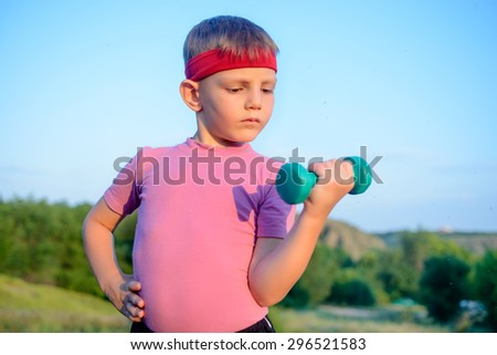 Close up Strong Cute Boy with Red Headband Doing an Outdoor Exercise and Lifting Small Dumbbell Against Blurry Nature Background.