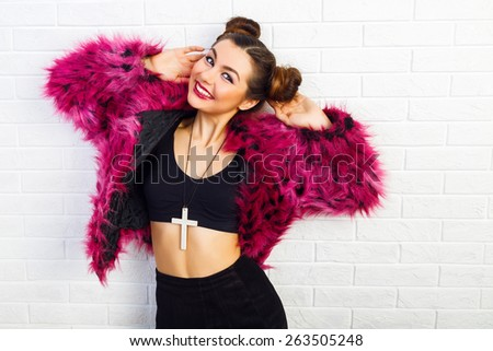 Close up studio funny portrait of young stylish sexy girl with cool hairstyle and bright trendy make up, wearing stylish fake fur coat, eighties style. - stock photo