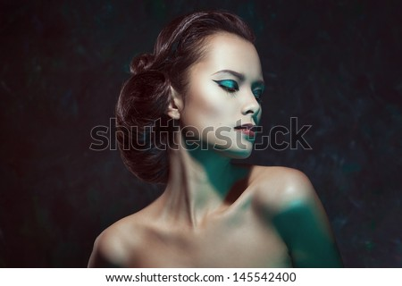 Close up studio portrait of a beautiful brunette woman with bright make up - stock photo