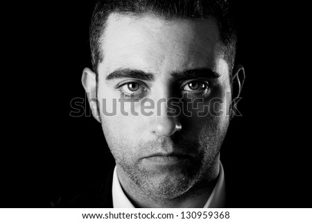 Close up studio portrait of a serious man on black background