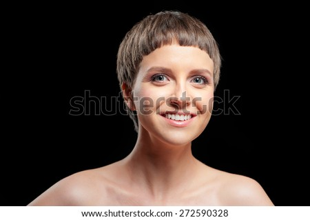 Close up studio Portrait of beautiful smiling young shirtless woman with short hair looking at camera while standing against black background - stock photo
