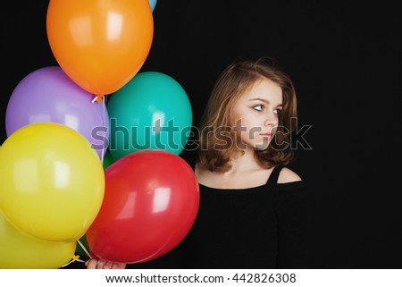 Close up studio portrait of beautiful teenage blond girl with colorful balloons over black background - stock photo