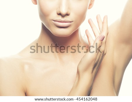 Close-up studio portrait of beautiful young caucasian brunette woman with natural lips and make-up isolated on white. Naked shoulders. Touch her perfect skin. Toned - stock photo
