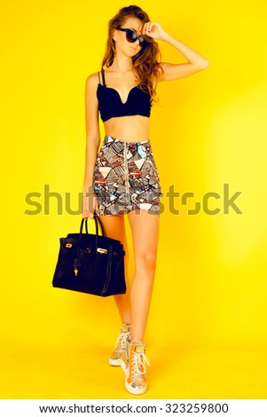 Close up studio portrait of cheerful blonde hipster girl going crazy making funny face,posing at cool urban outfit.Fashionable young lady,crop top,bright skirt,big  black bag,cat eyes sunglasses,bag - stock photo