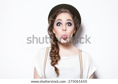 Close up studio portrait of cheerful brunette hipster girl against a wall  - stock photo