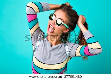 Close up studio portrait of funny joyful girl having fun imitated ponytails and shoving long tongue, bright make up, sunglasses, spring pastel colors. - stock photo