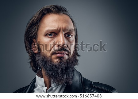 Close up studio portrait of serious, bearded male on grey background.