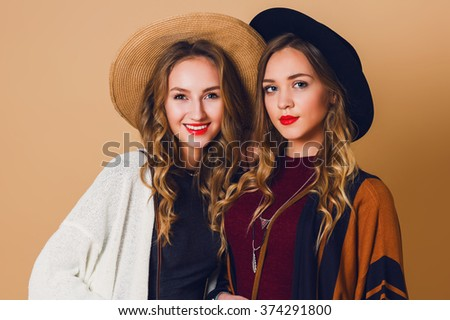 Close up studio portrait of two  sisters with blond wavy hairstyle in wool and straw hat wearing striped poncho. American or Australian hippie bohemian style. Girls laughing  and looking  at camera. - stock photo