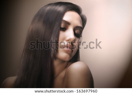 close-up studio portrait of young beautiful female face with long beauty glossy dark hair