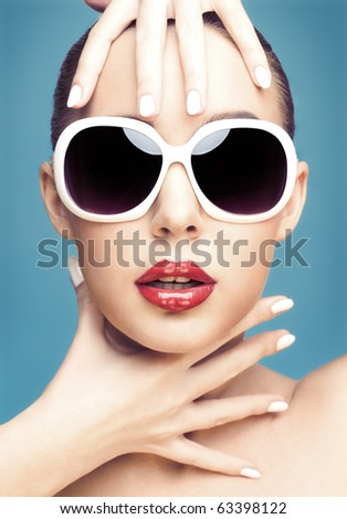 close up studio portrait of young beautiful woman wearing white sunglasses - stock photo