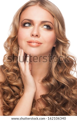 Close-up studio portrait of young beautiful woman with stylish golden makeup and hairstyle