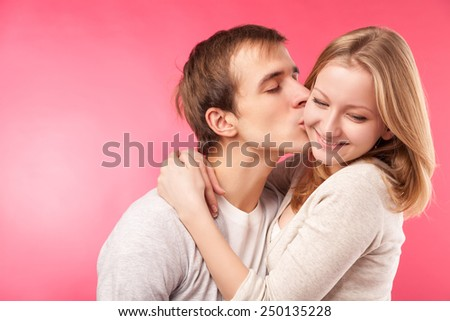 Close up studio portrait of young boy kissing cute girlfriend on cheek. Isolated on pink background. - stock photo