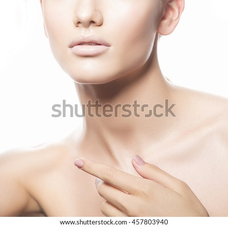 Close-up studio portrait of young caucasian brunette woman with natural lips, make-up and blue eyes isolated on white. Touch her perfect skin. Studio portrait. - stock photo