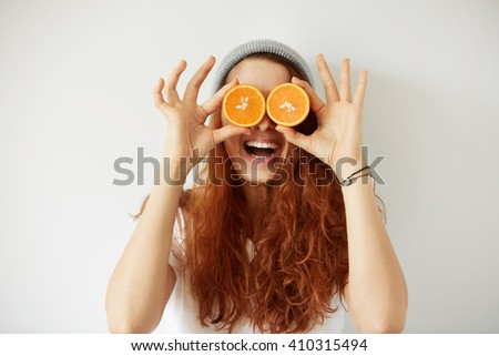 Close up studio portrait of young smiling female holding halves of oranges at her eyes. Headshot of pretty girl with loose red hair in cap and white T-shirt having fun. Film effect, selective focus  - stock photo