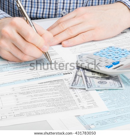 Close up studio shot of a male filling out 1040 US Tax Form - stock photo