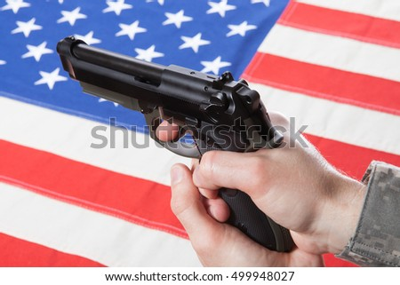 Close up studio shot of gun in hand with flag on background - USA