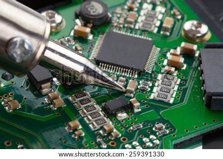 Close up studio shot of soldering iron and microcircuit - stock photo