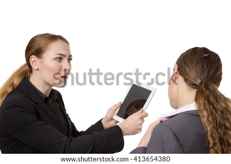 Close up studio shot of two pretty business women.  One is looking very concerned about the tablet computer in her hand.  The other woman is seen from behind.  isolated on white - stock photo