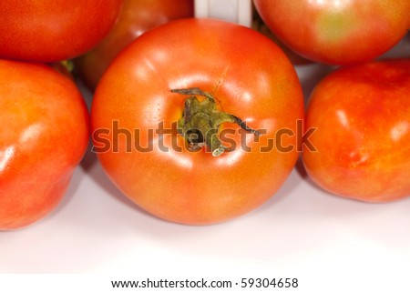 Close up studio view of some ripe tomatoes.