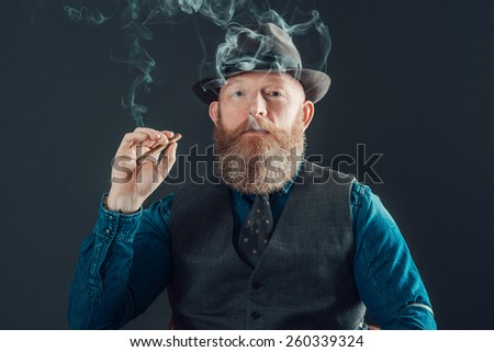 Close up Stylish Adult Man with Long Beard, in Denim Long Sleeves Shirt with Gray Vest and Cap, Smoking a Cigarette While Looking at the Camera. Isolated on a Gray Background. - stock photo